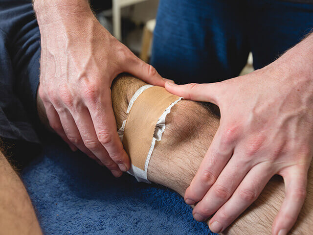 A knee is strapped to encourage healing after surgery