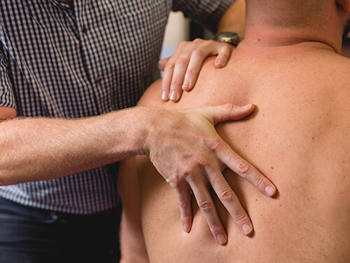The physiotherapist manipulates his patient's upper back and shoulders