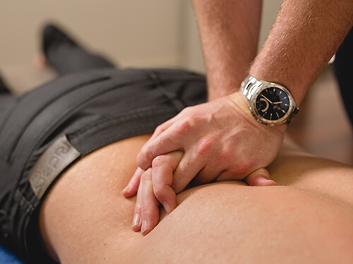 The physiotherapist manipulates the patient's lower back to alleviate pain
